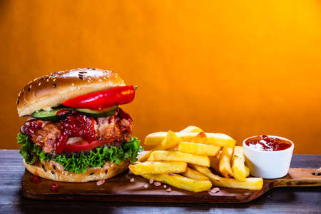 Tasty burger with chips served on cutting board Stockfoto - 129243590