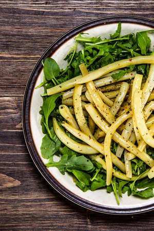 Yellow beans with arugula on wooden background