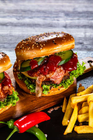 Tasty burgers with chips served black stone plate Фото со стока - 129824007