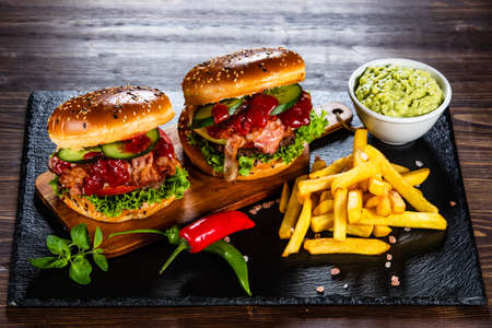 Tasty burgers with chips served black stone plate