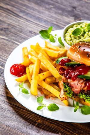 Tasty burger with chips served white plate Stock Photo - 129834421