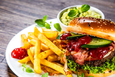 Tasty burger with chips served white plate Stock Photo - 129834422
