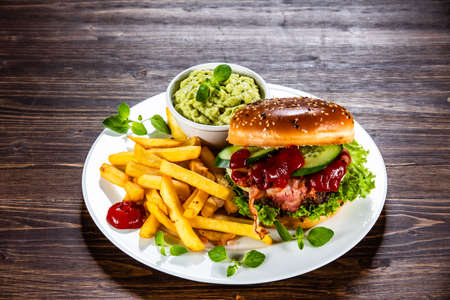 Tasty burger with chips served white plate