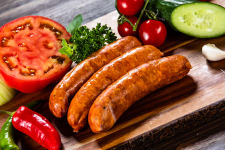 Raw sausages and vegetables on cutting board