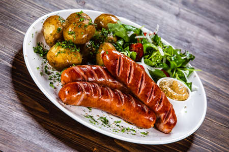 Salsicce alla griglia, patate al forno e verdure Archivio Fotografico