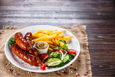 Grilled sausages, French fries and vegetables