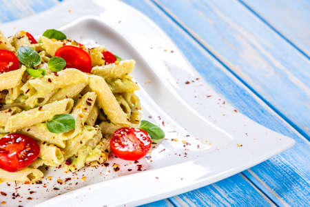 Pasta with herbs and vegetables on wooden background