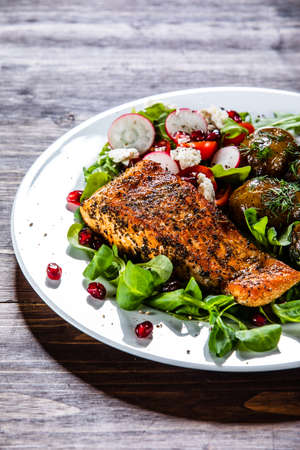 Grilled salmon, baked potatoes and vegetable salad Imagens