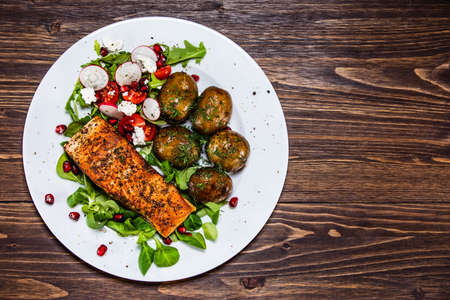 Grilled salmon, baked potatoes and vegetable salad Stok Fotoğraf - 130569157