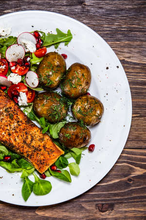 Grilled salmon, baked potatoes and vegetable salad Фото со стока - 129823028