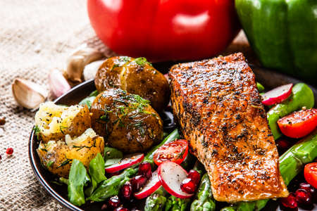Grilled salmon, baked potatoes and vegetable salad Stok Fotoğraf - 130569250