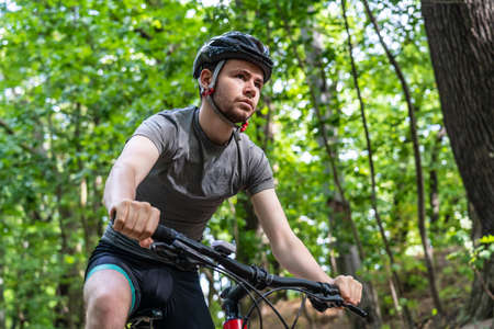 Young man biking in forest on red bike