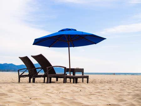 Deck chairs on beach with umbrella Фото со стока
