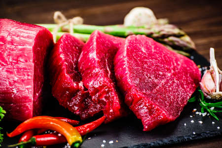 Fresh raw beef steaks with asparagus on wooden background