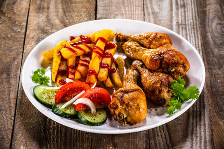 Grilled chicken drumsticks with french fries and vegetables