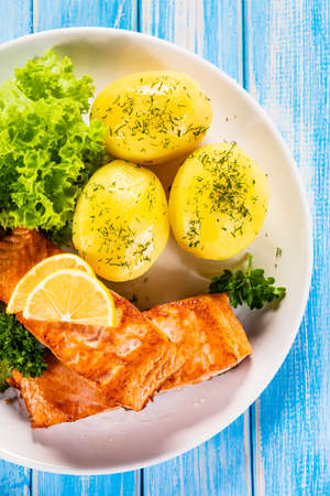Grilled salmon with boiled potatoes and vegetable salad Stockfoto - 130119626