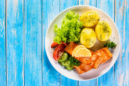 Grilled salmon with boiled potatoes and vegetable salad