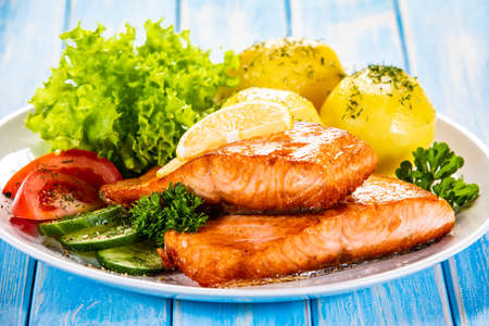 Grilled salmon with boiled potatoes and vegetable salad Stockfoto - 130119692