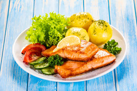 Grilled salmon with boiled potatoes and vegetable salad Stockfoto - 130119695