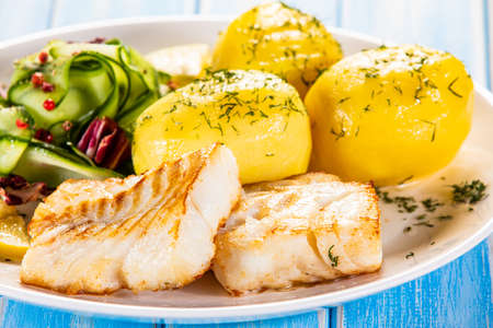 Fried fish with potatoes and vegetable salad on white plate on blue planks