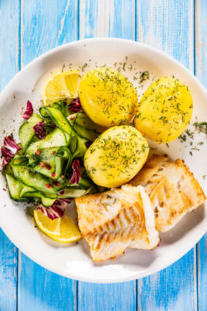 Fried fish with potatoes and vegetable salad on white plate on blue planks Stockfoto - 130119733