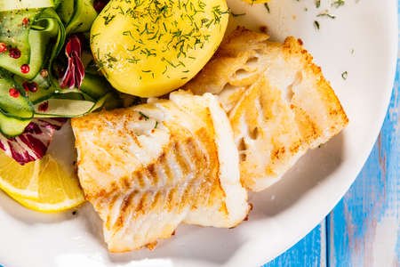 Fried fish with potatoes and vegetable salad on white plate on blue planks Stockfoto - 130119734