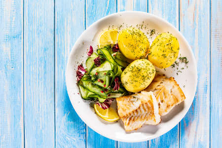 Fried fish with potatoes and vegetable salad on white plate on blue planks Stockfoto - 130119735