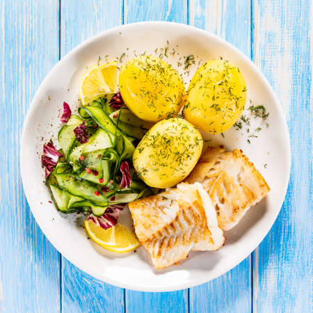 Fried fish with potatoes and vegetable salad on white plate on blue planks Stockfoto - 130119738