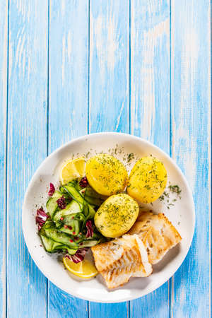 Fried fish with potatoes and vegetable salad on white plate on blue planks Stockfoto - 130119736