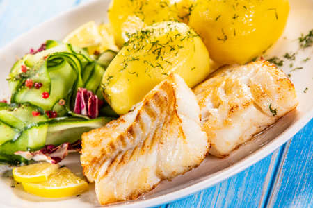 Fried fish with potatoes and vegetable salad on white plate on blue planks Stockfoto - 130119737