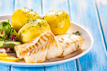 Fried fish with potatoes and vegetable salad on white plate on blue planks Stockfoto - 130119740