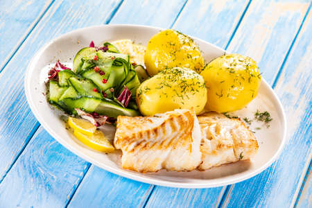 Fried fish with potatoes and vegetable salad on white plate on blue planks Stockfoto - 130119739