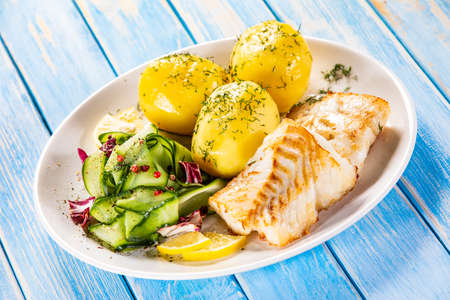 Fried fish with potatoes and vegetable salad on white plate on blue planks Stockfoto - 130119744