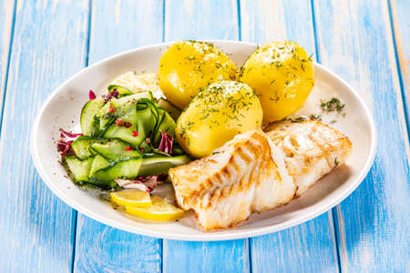 Fried fish with potatoes and vegetable salad on white plate on blue planks Stockfoto - 130119741