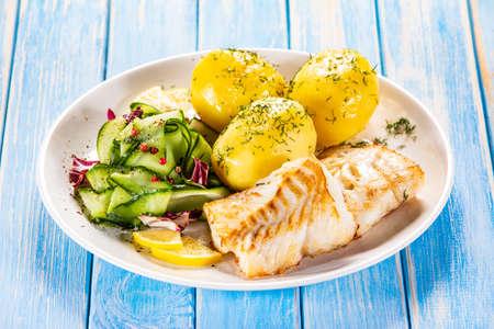 Pesce fritto con patate e insalata di verdure su piatto bianco su tavole blu Archivio Fotografico
