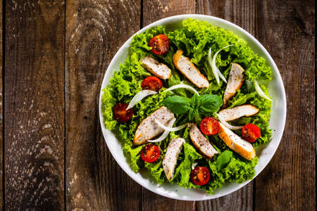 Caesar salad on white plate on wooden table Фото со стока