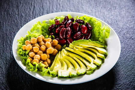 Vegetable salad with chickpea, avocado and red beans in bowl on black stone