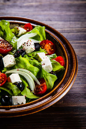 Greek salad in bowl on wooden table