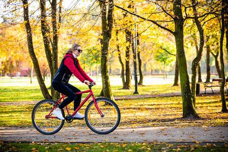 Urban biking - woman riding bike in city park Imagens