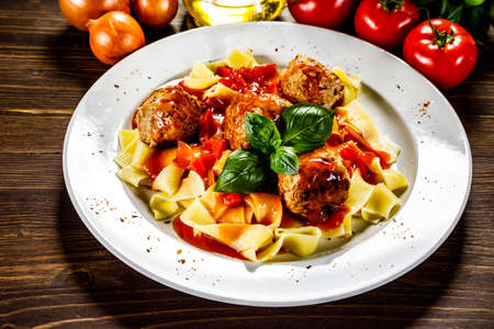 Pasta with meatballs on wooden background