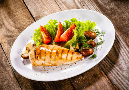 Grilled chicken fillet and vegetables on white plate