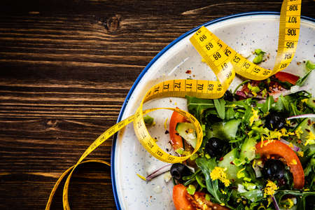 Vegetable salad with rucola and tomatoes with measuring tape on it