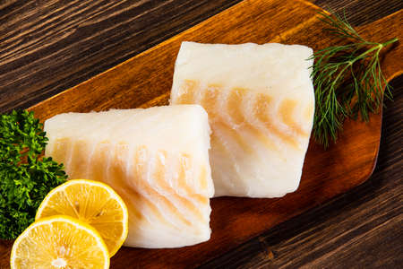 Fresh raw cod served on cutting board on wooden table. Fresh raw cod served on cutting board on wooden table Stock Photo