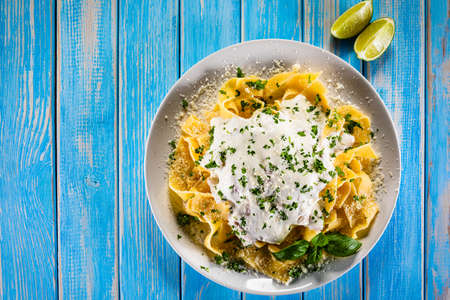 Tagliatelle with cream sauce and herbs on wooden table