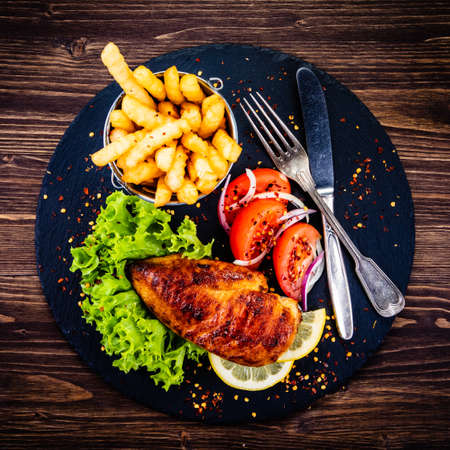 Grilled chicken fillet with french fries on wooden table Banco de Imagens - 132051390