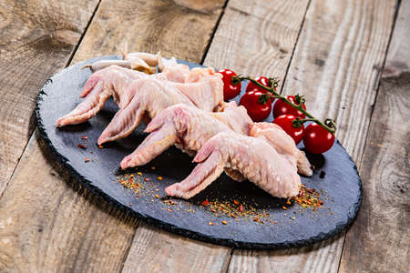 Raw chicken wings on black stone on wooden background 版權商用圖片
