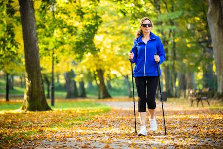 노르딕 워킹 - 도시 공원에서 운동하는 중년 여성
