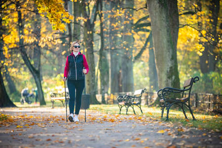 Nordic walking - middle-age woman working out in city park Reklamní fotografie