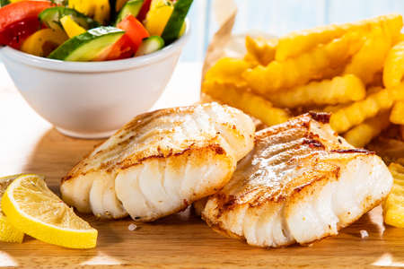 Fish dish - fried fish fillet with french fries and vegetables Stock Photo