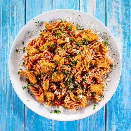 Fusilli with meat and vegetables on wooden table